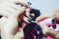 Manicure. Beauty saloon. Close-up. Apply black nail polish. Stock Photos