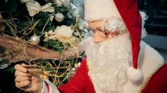 Santa Claus with a cash card near Christmas tree Stock Footage