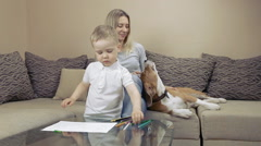 Child painting at the table with mother and dog Stock Footage