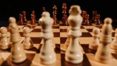 A chess board and it´s pieces lined up, the shot is taken behind white pieces Stock Footage