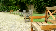 View of the large evergreen park in the suburb - many different wooden benches Stock Footage
