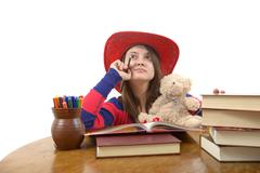 young meditative girl with red hat and her teddy bear at the table with books - stock photo