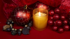 New Year's composition on a red background - ball and ribbon and a candle - stock footage