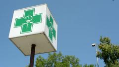 view of the pharmacy symbol on the rod in the street - plus and snake  - stock footage
