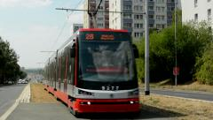 Modern streetcar passes through the housing estate in the suburb Stock Footage