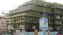 View of the scaffolding by the high buidling in the suburb nearby the road Stock Footage