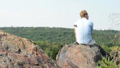 Young man sits on the high rock in the mountain - he looks around himself  Stock Footage