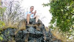 Young handsome man sits on the top of the mountain he writes messages on phone Stock Footage
