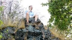Young handsome man sits on the top of the mountain he call with phone Stock Footage