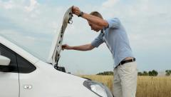 Young handsome man opens hood of modern car and checks engine in the countryside Stock Footage