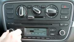 Man controls the panel of buttons of the car - maximum and minimum of radio Stock Footage
