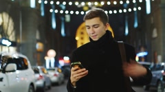 The man smiles, looks at his phone: sms reading, working with gadget Stock Footage