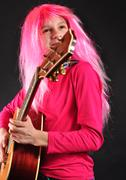 Stock Photo of teenager with pink hair playing guitar