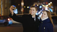 Young couple photographing self against the backdrop of the city at night Stock Footage