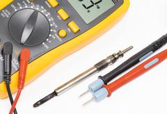 Old Diesel engine glow plug and multimeter - stock photo