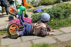 The little boy fell off the bike at first individual driving. - stock photo