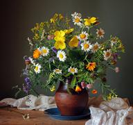Still life with a summer bouquet of wild flowers in a clay jug. - stock photo