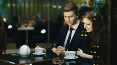 Young couple in a cafe drinking tea, looking at mobile phone screen Arkistovideo