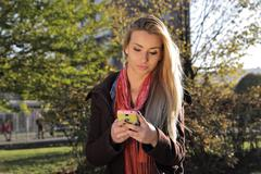 Outdoor portrait of a beautiful Caucasian girl sms texting at phone Stock Photos