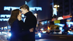 Young couple kissing on the background of the city at night and blurry lights - stock footage