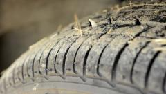 Detail of car tire - grass between tread Stock Footage