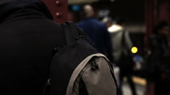 man with backpack and headphones waiting for train on subway station platform - stock footage