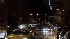 taxi cab at night - lower Fifth Avenue with Empire State Building in distance NY - stock footage