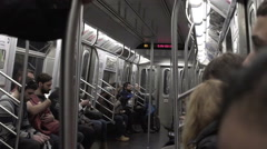 Interior subway carriage with variety of people riding, racial diversity in NYC Stock Footage