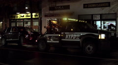 NYPD tow truck with car latched on back driving away on 8th street in New York Stock Footage