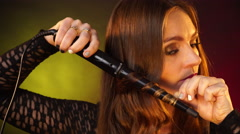 Stock Video Footage of Woman making hairstyle with electric hair curler iron 4K