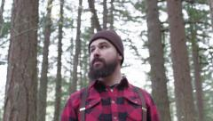 Mountain Man surveys the forest while holding his axe Stock Footage