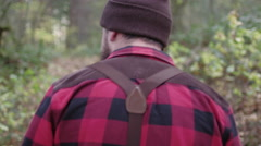 Mountain man hikes through the forest and surveys the land - stock footage