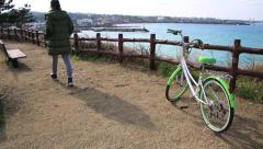 Woman in training suit passing by a bicycle and sitting on the bench by ocean Stock Footage