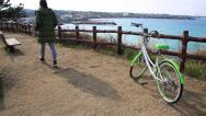 Stock Video Footage of Woman in training suit passing by a bicycle and sitting on the bench by ocean