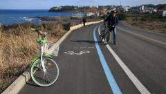 A bicycle parking on bike-only road by ocean and cars passing on the road Stock Footage