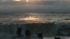 Sunset on beach in England with waves lapping up over wooden groins Stock Footage