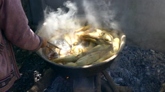 Boiling corn cobs into a wok for selling cooked sweet corn in Thailand - stock footage