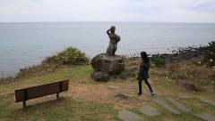 Woman walking and resting on the bench by the statue of a female diver Stock Footage