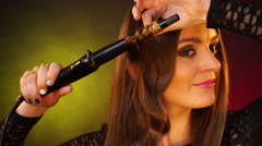 Woman making hairstyle with electric hair curler iron 4K Stock Footage