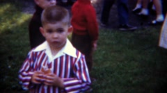 1953: 4th of July party boy dressed in patriotic stripes eating hotdog. - stock footage