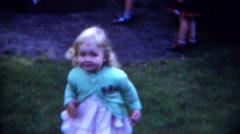1953: Cute blonde toddler running wild eating hotdog at summer picnic. PITTSBURG - stock footage