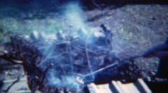 1953: Girl cooking hotdog over wood burning campfire hobo style. PITTSBURG - stock footage