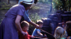1953: Kids weenie roasting party hotdog condiments tables roasting party. - stock footage