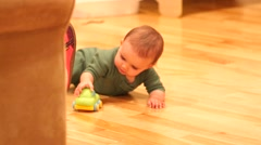 Baby playing on hardwood floor with a car Stock Footage