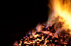 beautiful red hot glowing ember pile with colorful flames in winter night - stock photo