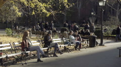 People park benches with Menorah cold fall winter day Washington Square Park NYC Stock Footage