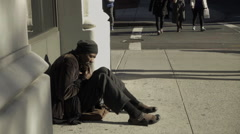 Homeless black man sitting on sidewalk with people walking by cold weather NYC Stock Footage