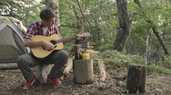 Caucasian man playing guitar at a camp site, Yamanashi Prefecture Stock Footage