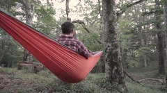 Slow motion footage of Caucasian man relaxing on a hammock at a camp site, Stock Footage