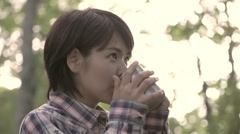 Slow motion footage of Japanese woman enjoying coffee at a camp site, Yamanashi Stock Footage